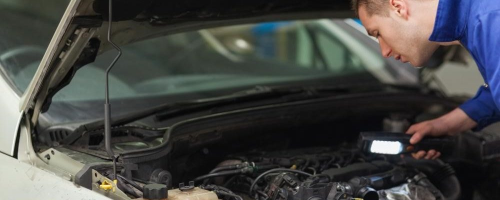 A mechanic checking the engine of a car